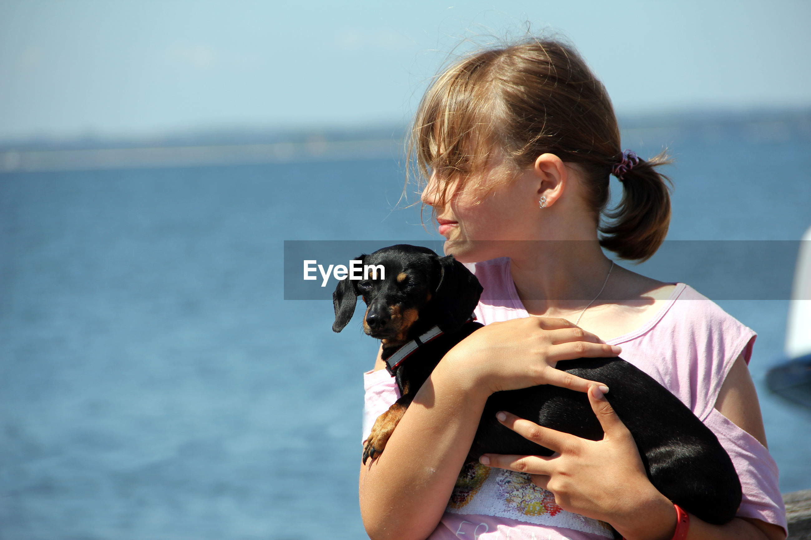 Girl carrying dachshund against sea