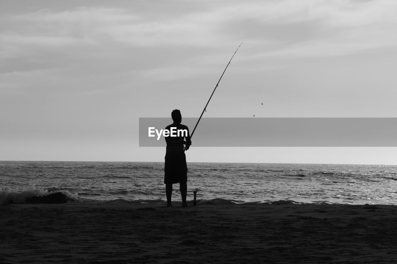 sea, real people, horizon over water, fishing, water, one person, nature, standing, leisure activity, men, beach, holding, sky, weekend activities, outdoors, lifestyles, tranquil scene, silhouette, beauty in nature, scenics, fishing pole, fishing tackle, day, full length, flying, adult, people