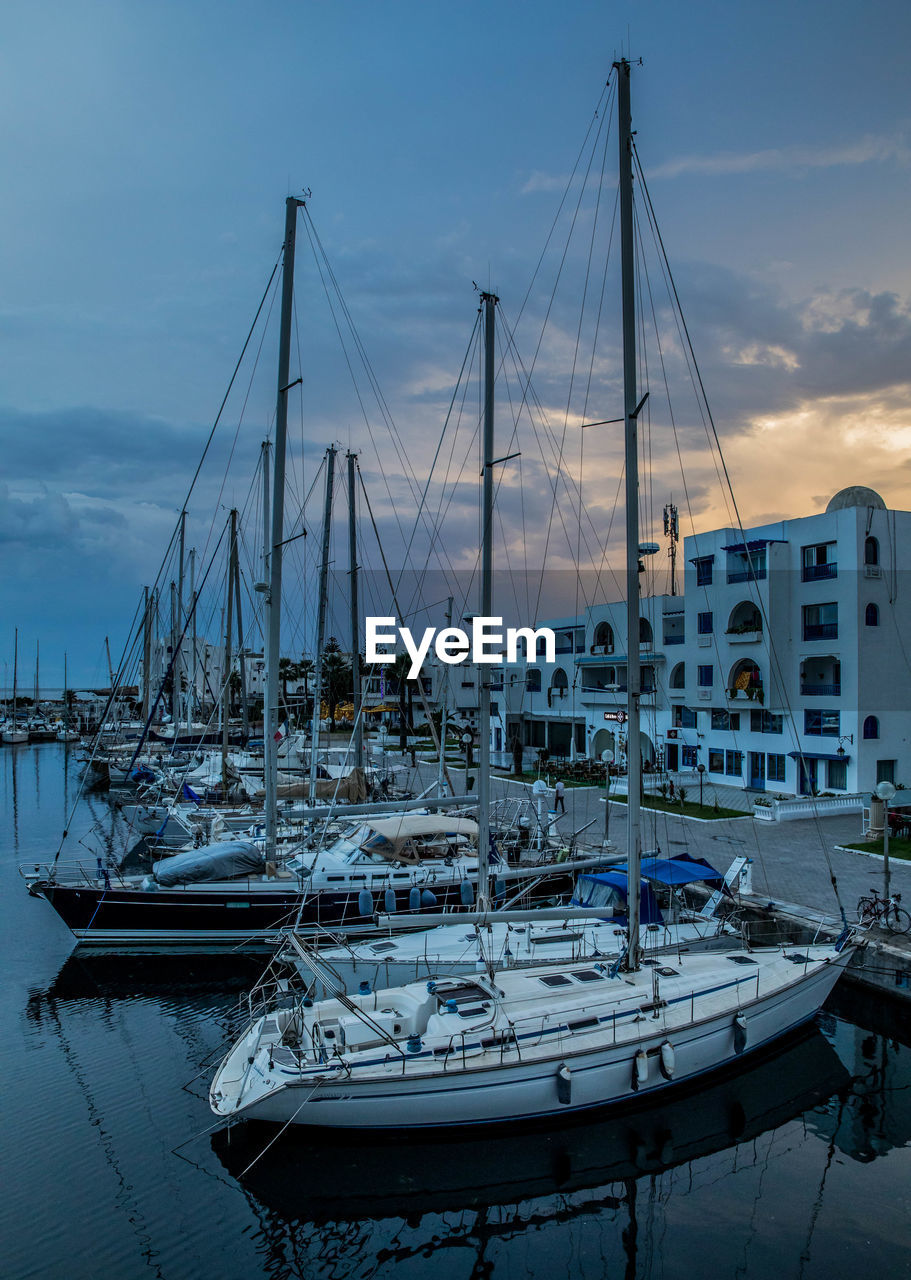 nautical vessel, transportation, water, mode of transportation, sky, sailboat, moored, mast, pole, harbor, cloud - sky, architecture, sea, nature, no people, built structure, sunset, building exterior, waterfront, outdoors, yacht, marina