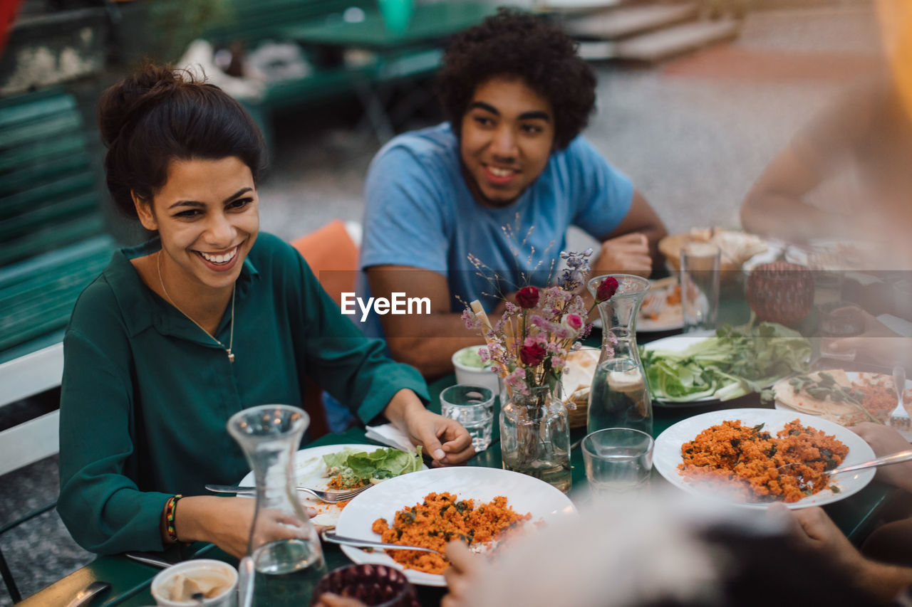 table, food and drink, plate, restaurant, togetherness, front view, business, real people, young women, women, food, sitting, indoors, two people, lifestyles, smiling, young adult, freshness, casual clothing, friendship, meal, glass, positive emotion