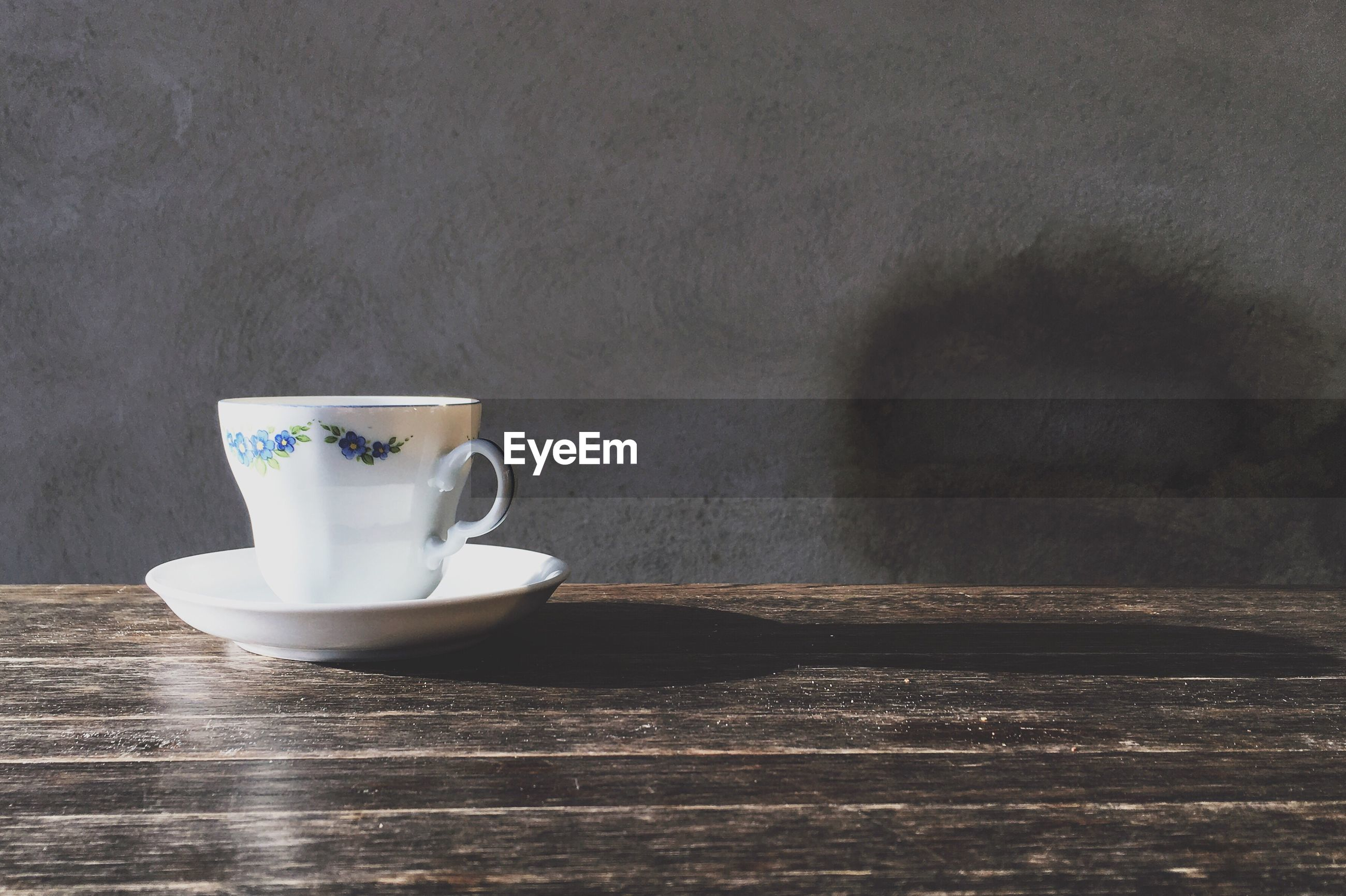 Coffee cup against wall on wooden table