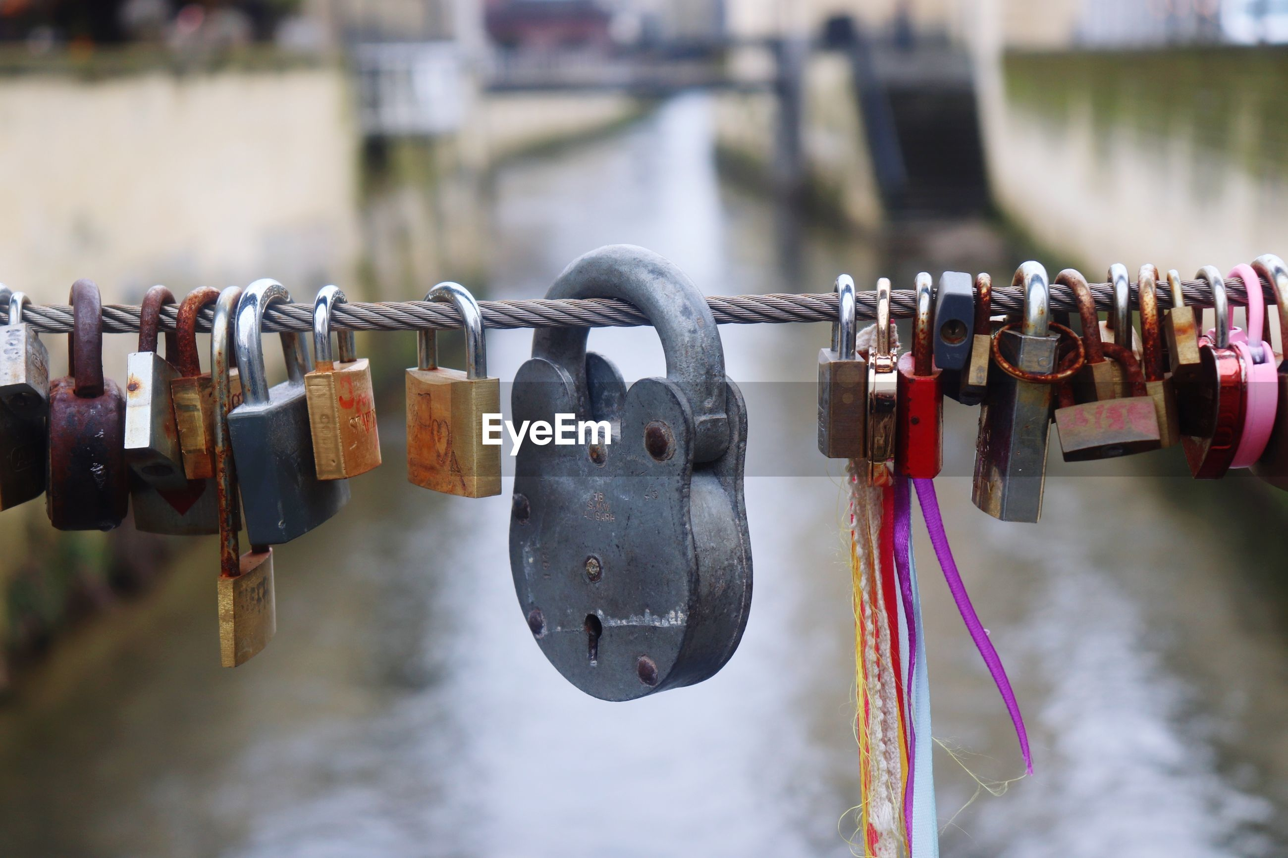 Close-up of padlocks on railing against river