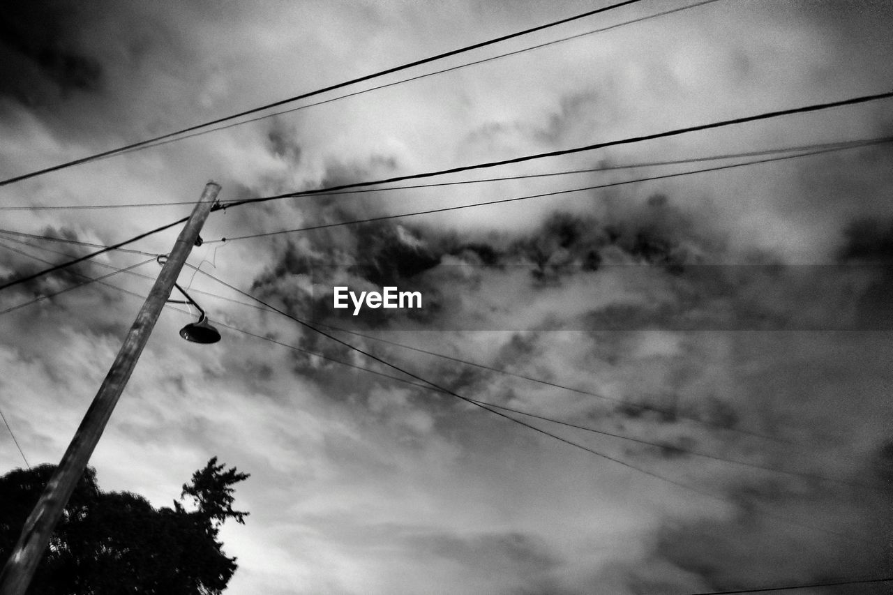 Low angle view of telephone pole by silhouette tree against sky