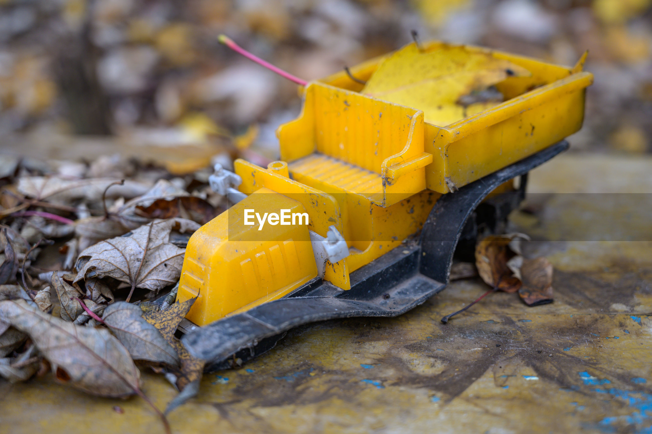 Close-up of yellow broken toy on land