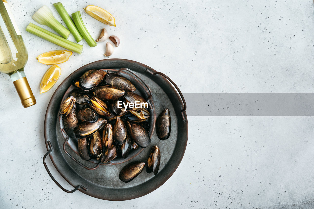 Shell mussels with vegetable ingredients on a textured white background.