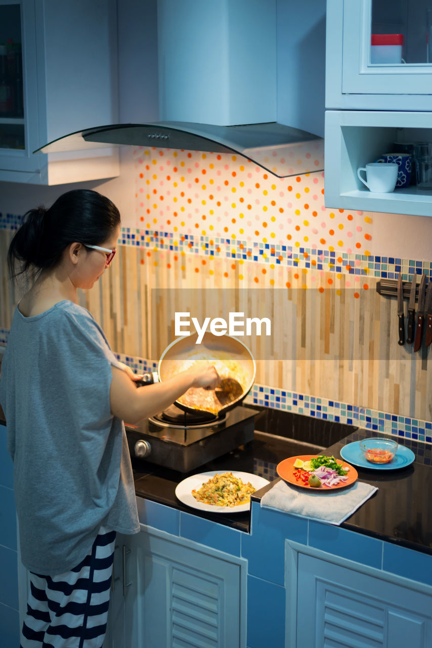 Woman serving food in plate at home