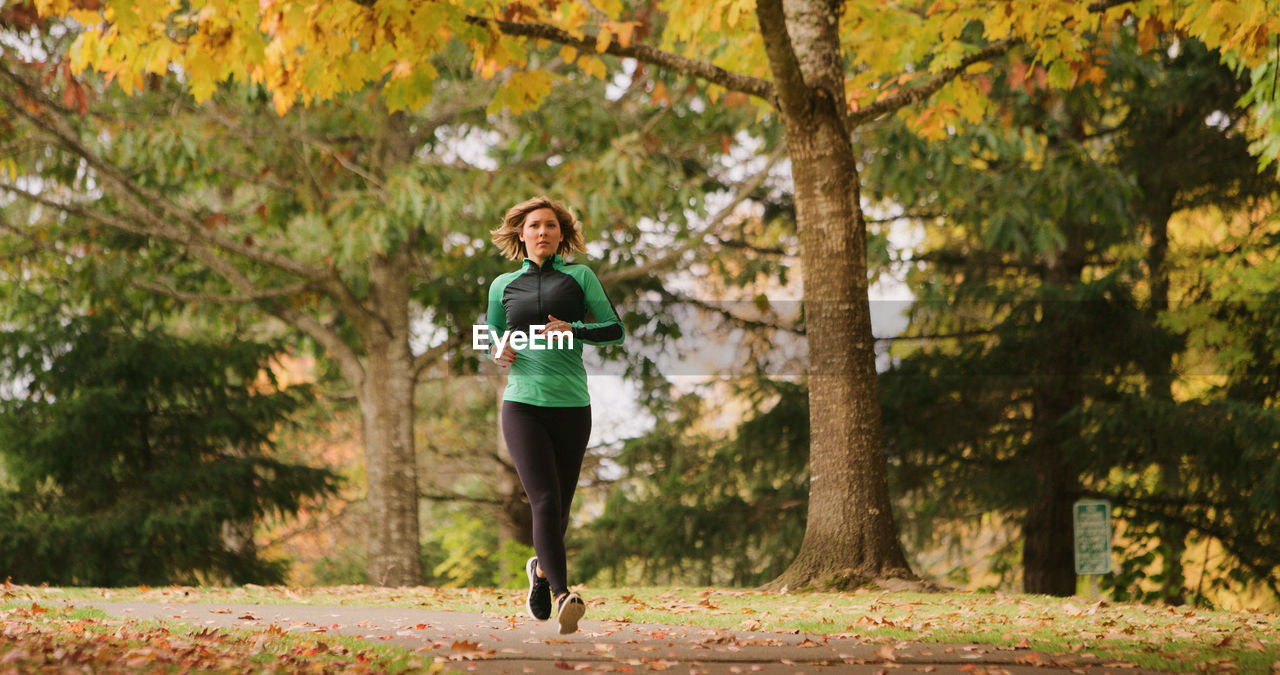Full Length Of Young Woman Jogging In Park During Autumn