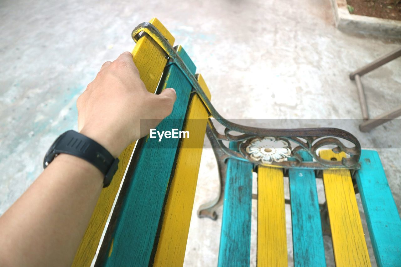 HIGH ANGLE VIEW OF PERSON HAND HOLDING YELLOW