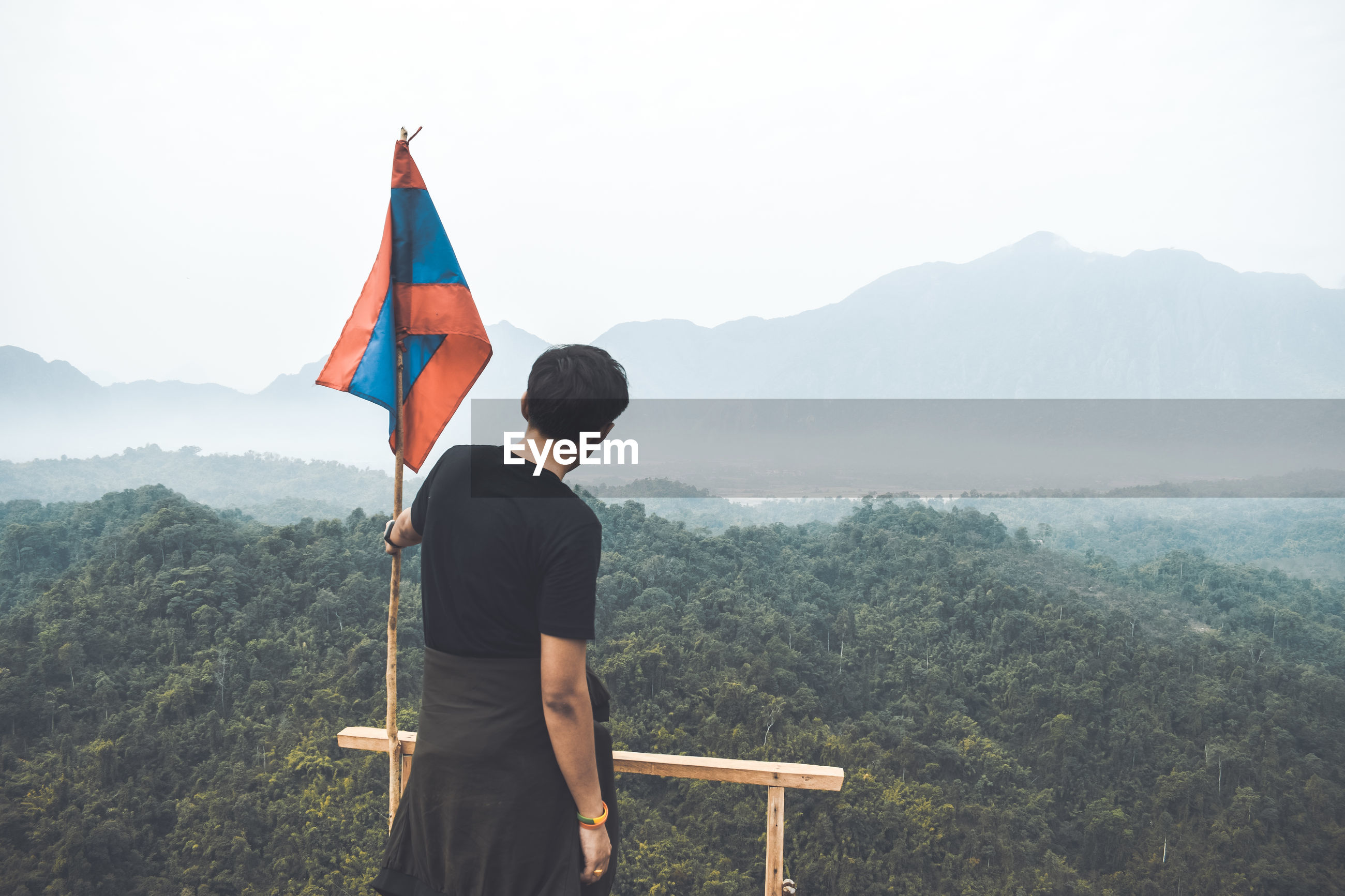 Rear view of man by flag standing on mountain against sky