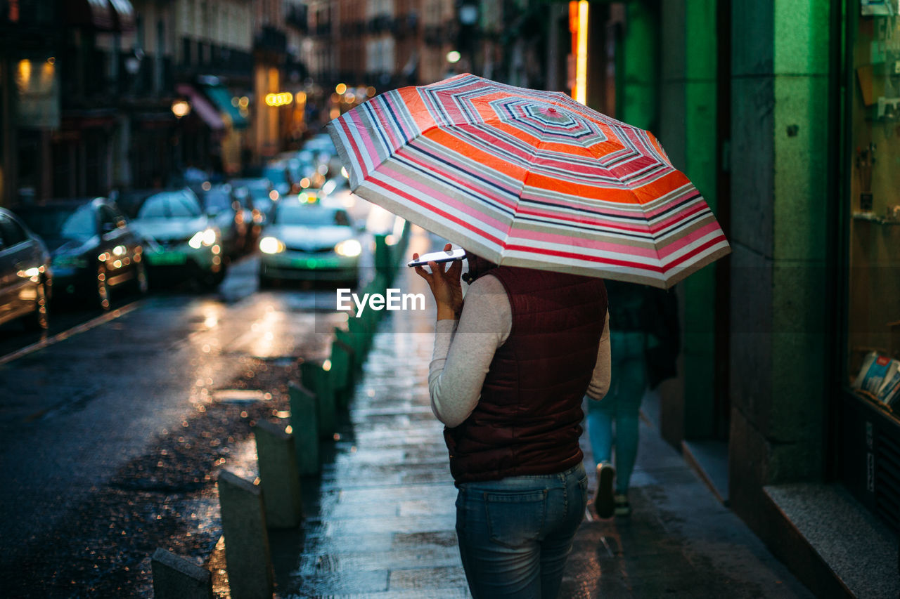 Woman Standing On Sidewalk During Rainy Season