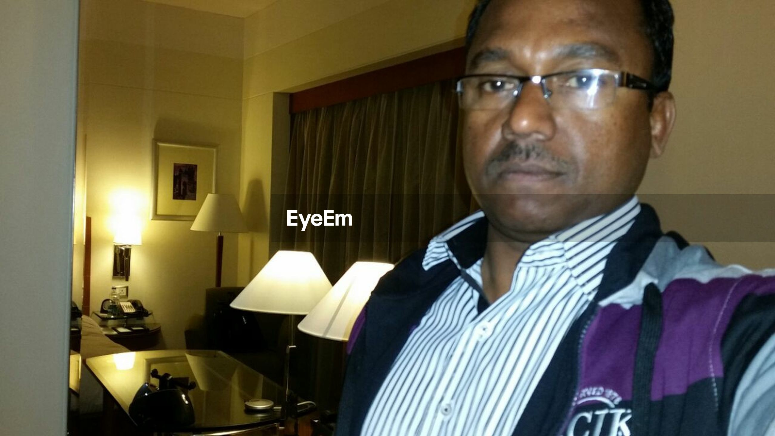 indoors, home interior, person, table, young adult, front view, sitting, chair, lifestyles, looking at camera, casual clothing, domestic room, restaurant, domestic life, leisure activity, young men, portrait, eyeglasses