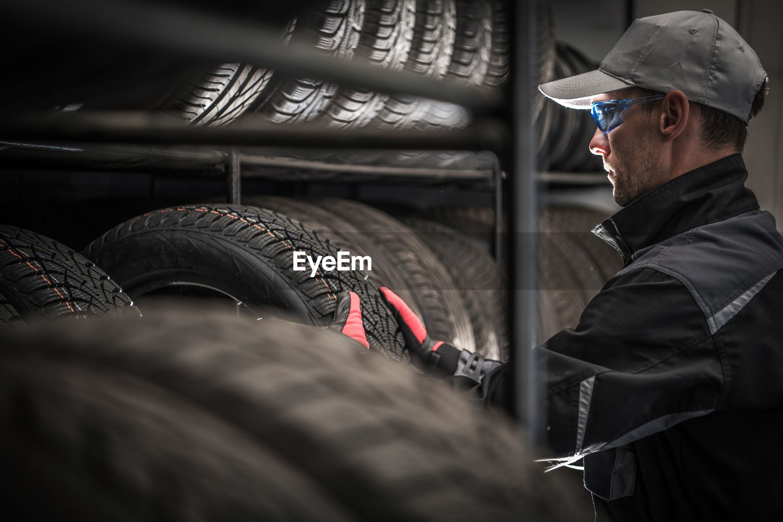 Male mechanic arranging tires on shelves in auto repair shop