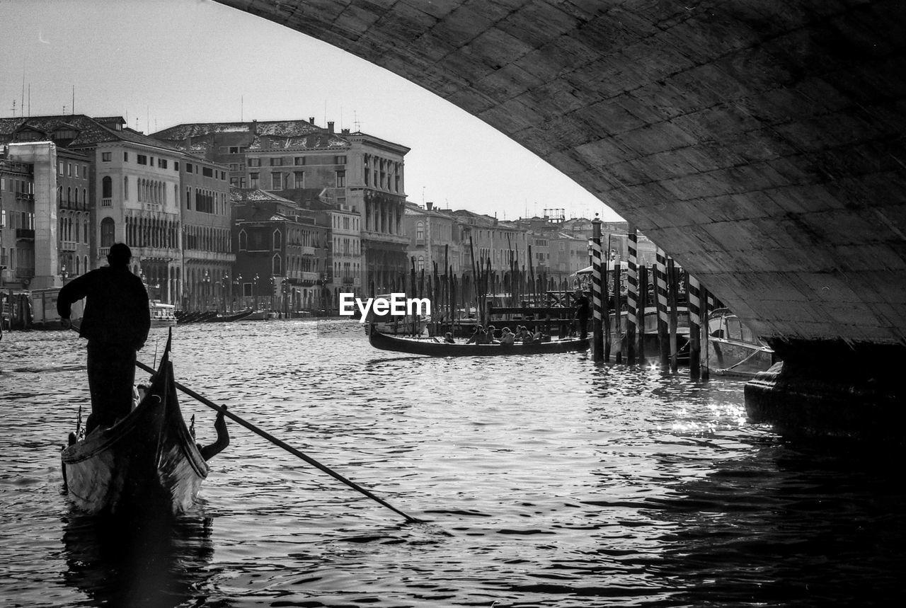 Man Sailing Gondola On Canal