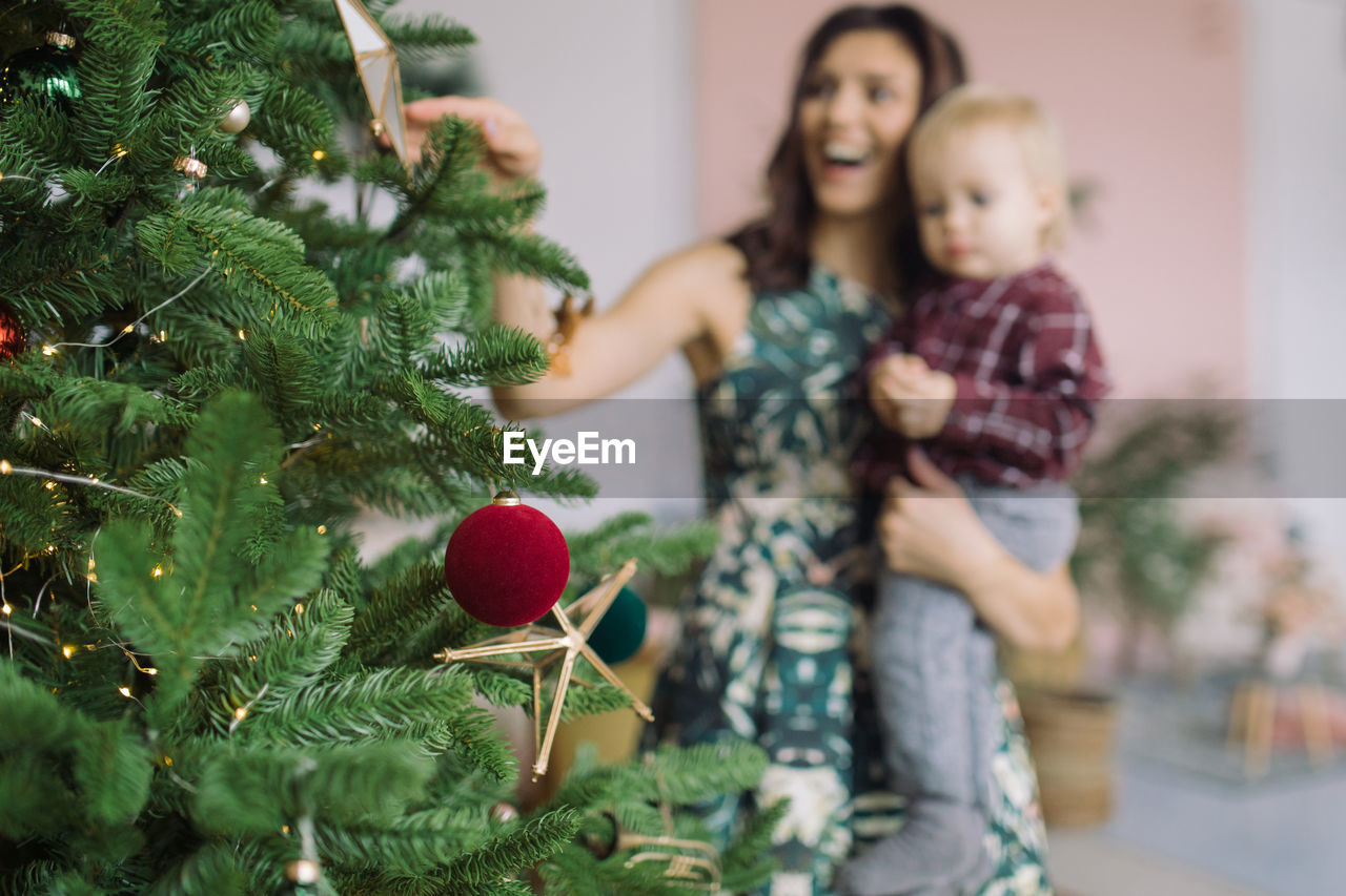 Cheerful Mother Carrying Son At Home With Christmas Tree In Foreground