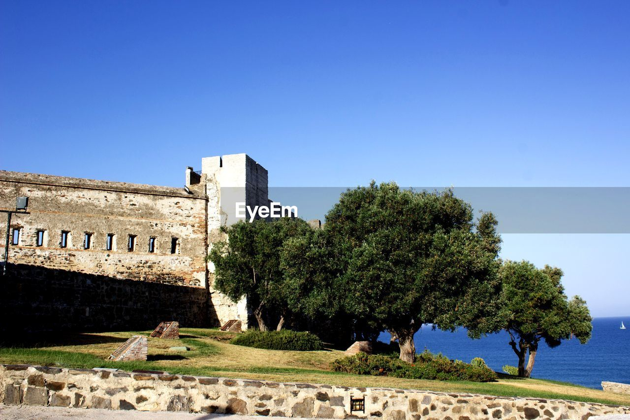 sky, architecture, built structure, clear sky, history, the past, nature, tree, building exterior, copy space, plant, day, blue, ancient, sunlight, travel destinations, travel, old ruin, fort, outdoors, no people, ancient civilization, ruined, ancient history