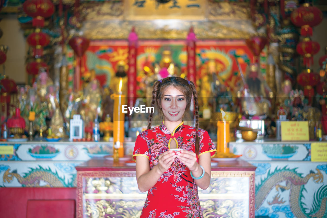 Portrait of smiling woman with tea light standing in temple