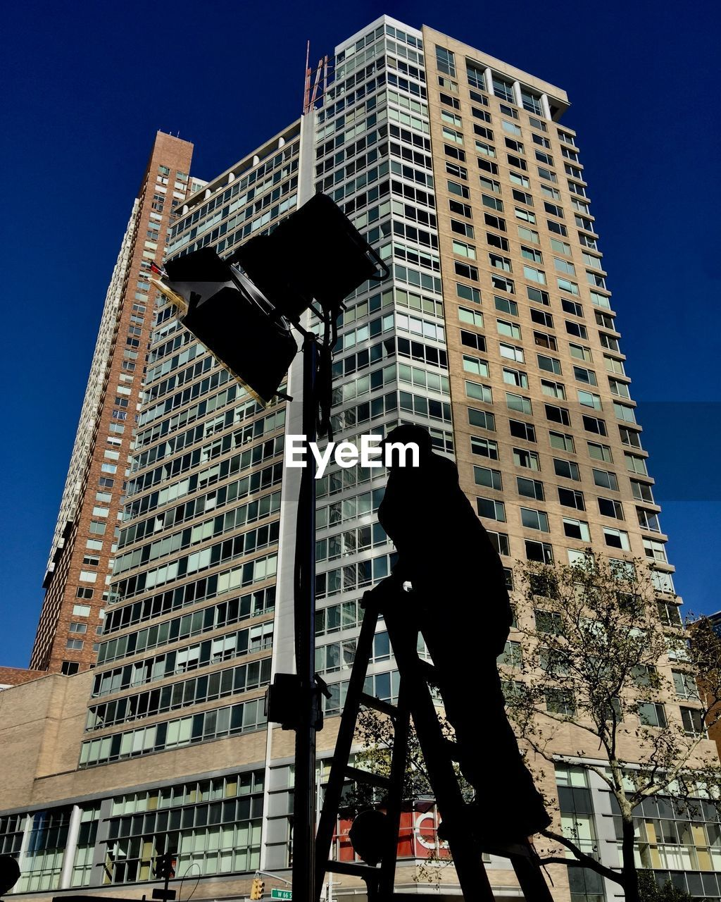 built structure, architecture, building exterior, building, low angle view, one person, city, real people, sky, nature, occupation, men, day, clear sky, office building exterior, outdoors, standing, sunlight, skyscraper