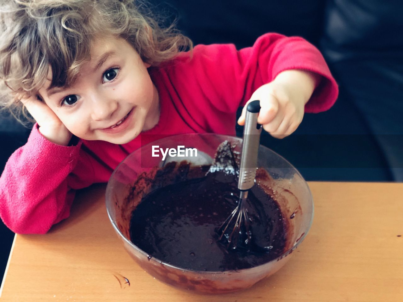 Cute girl holding wire whisk in bowl on table