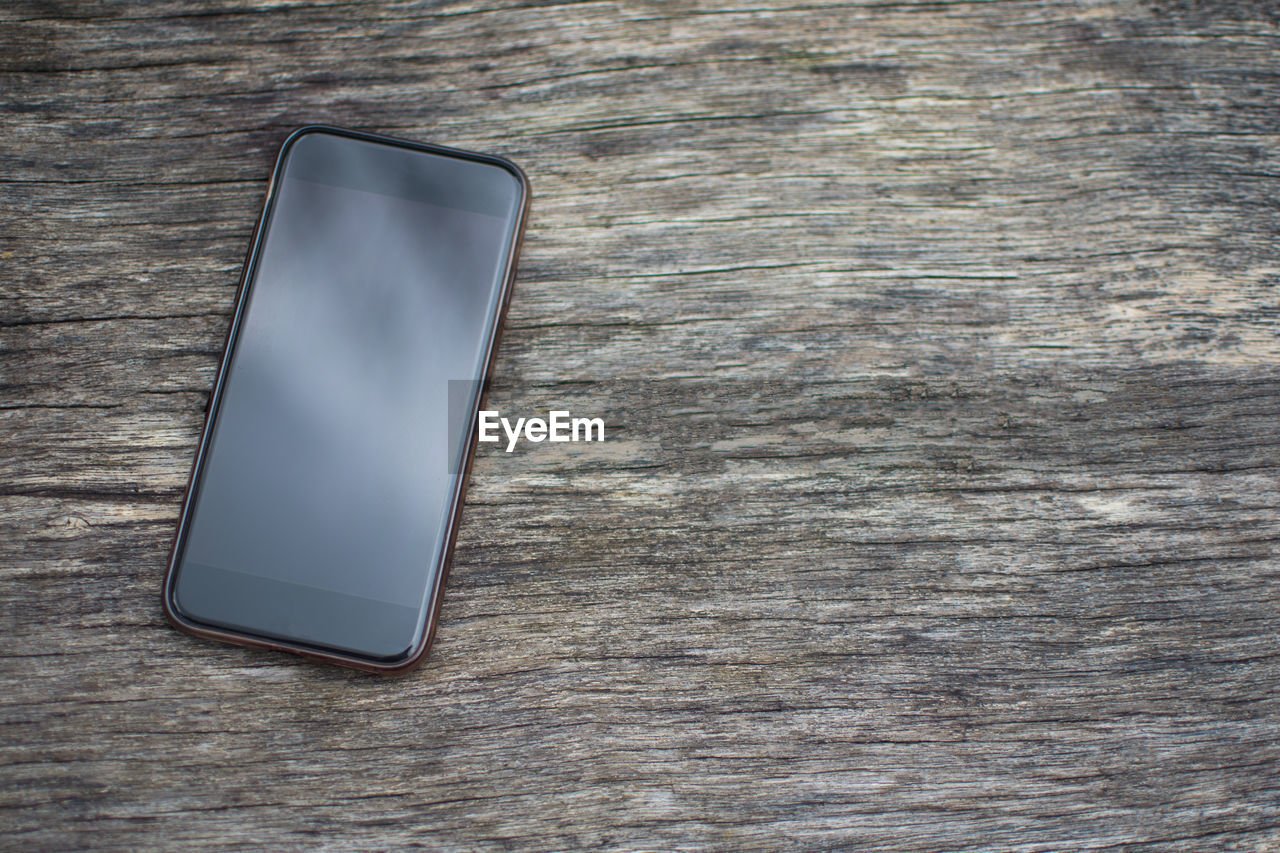 High angle view of smart phone on wooden table