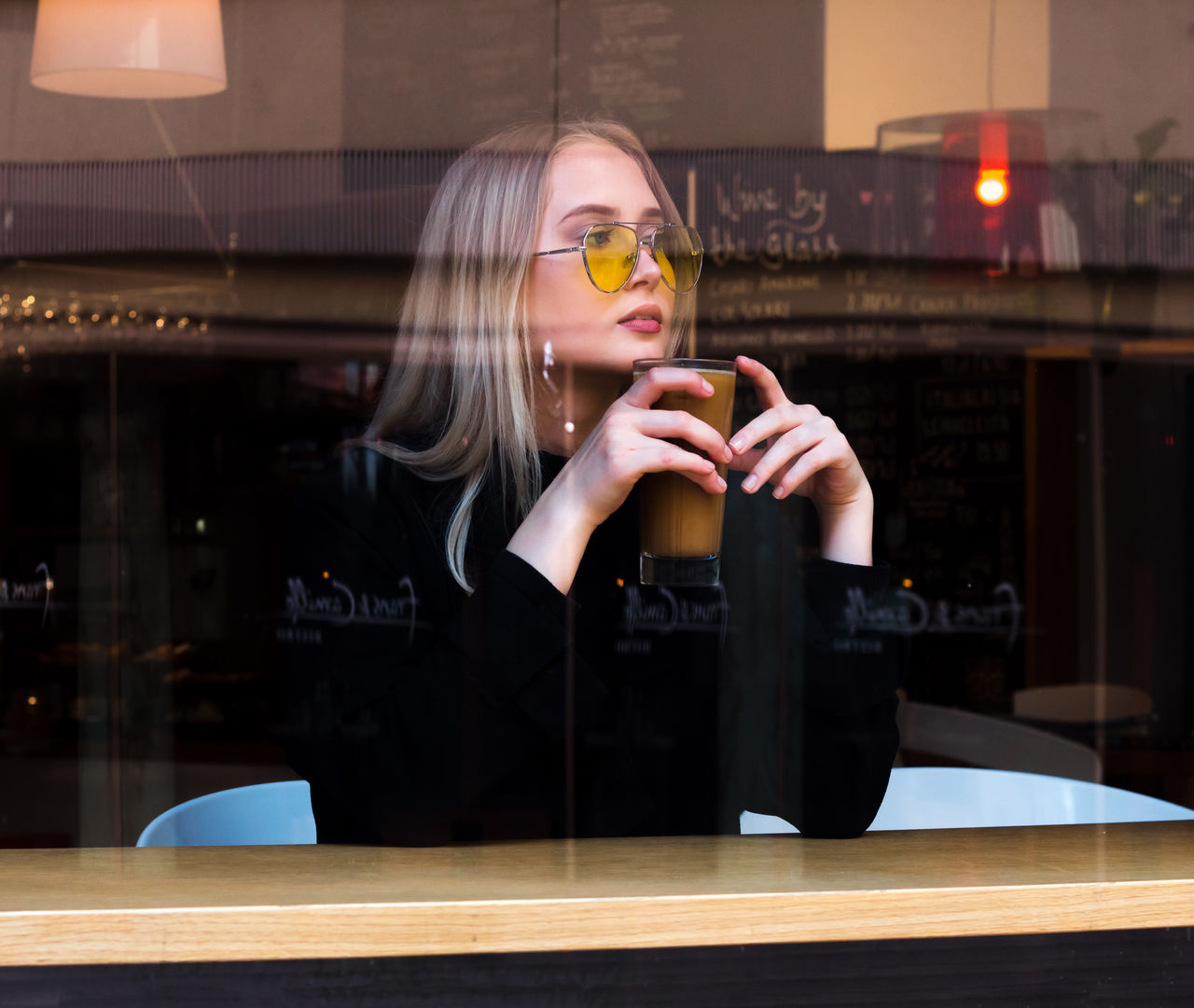 YOUNG WOMAN USING MOBILE PHONE AT WINDOW