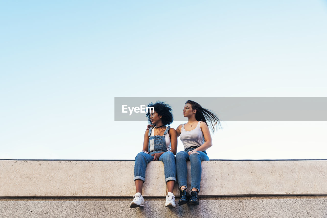 Female Friends Sitting On Retaining Wall Against Clear Sky