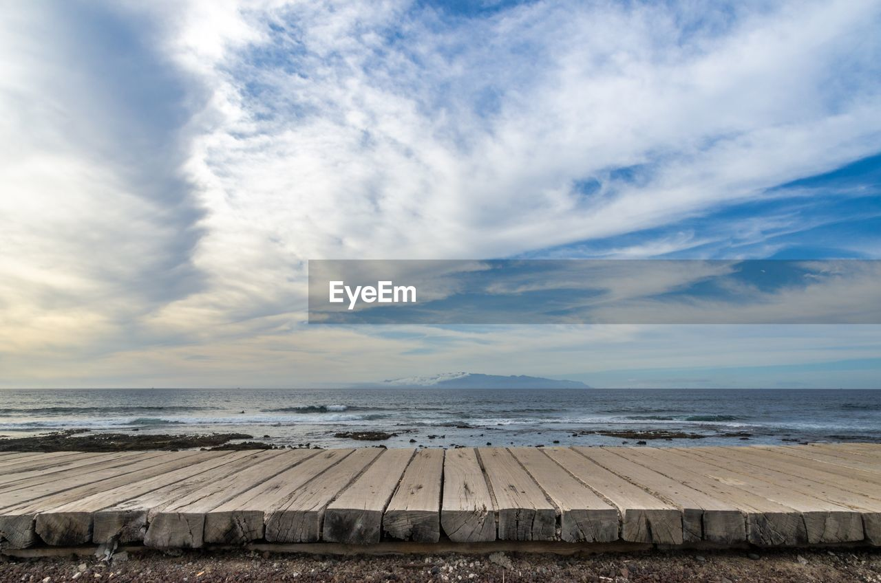 Boardwalk against the distant gomera island from the shore at playa de las americas in tenerife