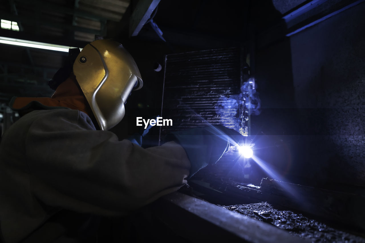 MAN WORKING AT ILLUMINATED FACTORY