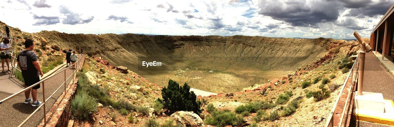Panoramic view of people on walkway in volcanic crater against sky