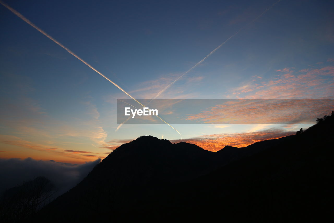 vapor trail, scenics, beauty in nature, nature, tranquil scene, contrail, majestic, sunset, mountain, tranquility, silhouette, no people, outdoors, sky, landscape, day