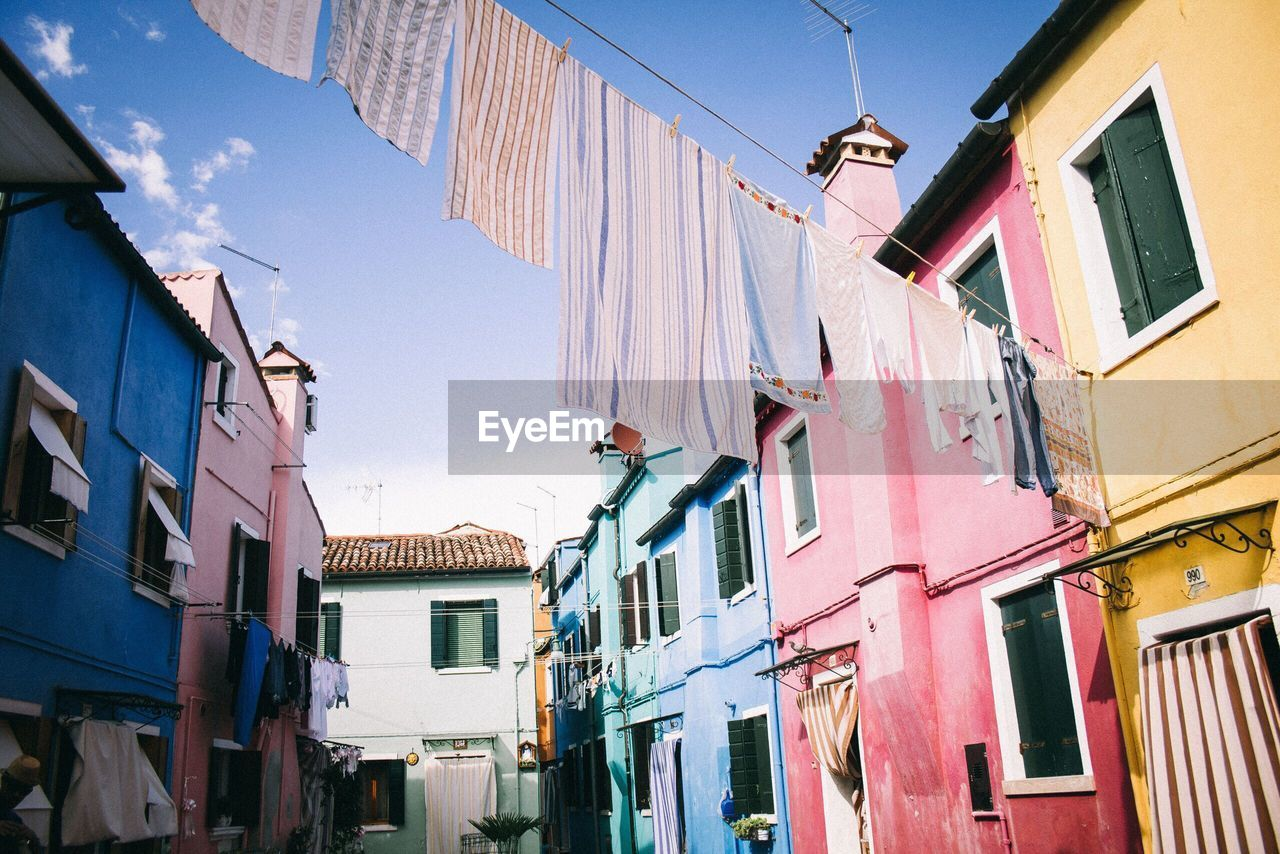 building exterior, architecture, built structure, building, low angle view, residential district, hanging, window, day, clothing, drying, clothesline, laundry, nature, no people, city, sky, outdoors, textile, sunlight, alley, row house