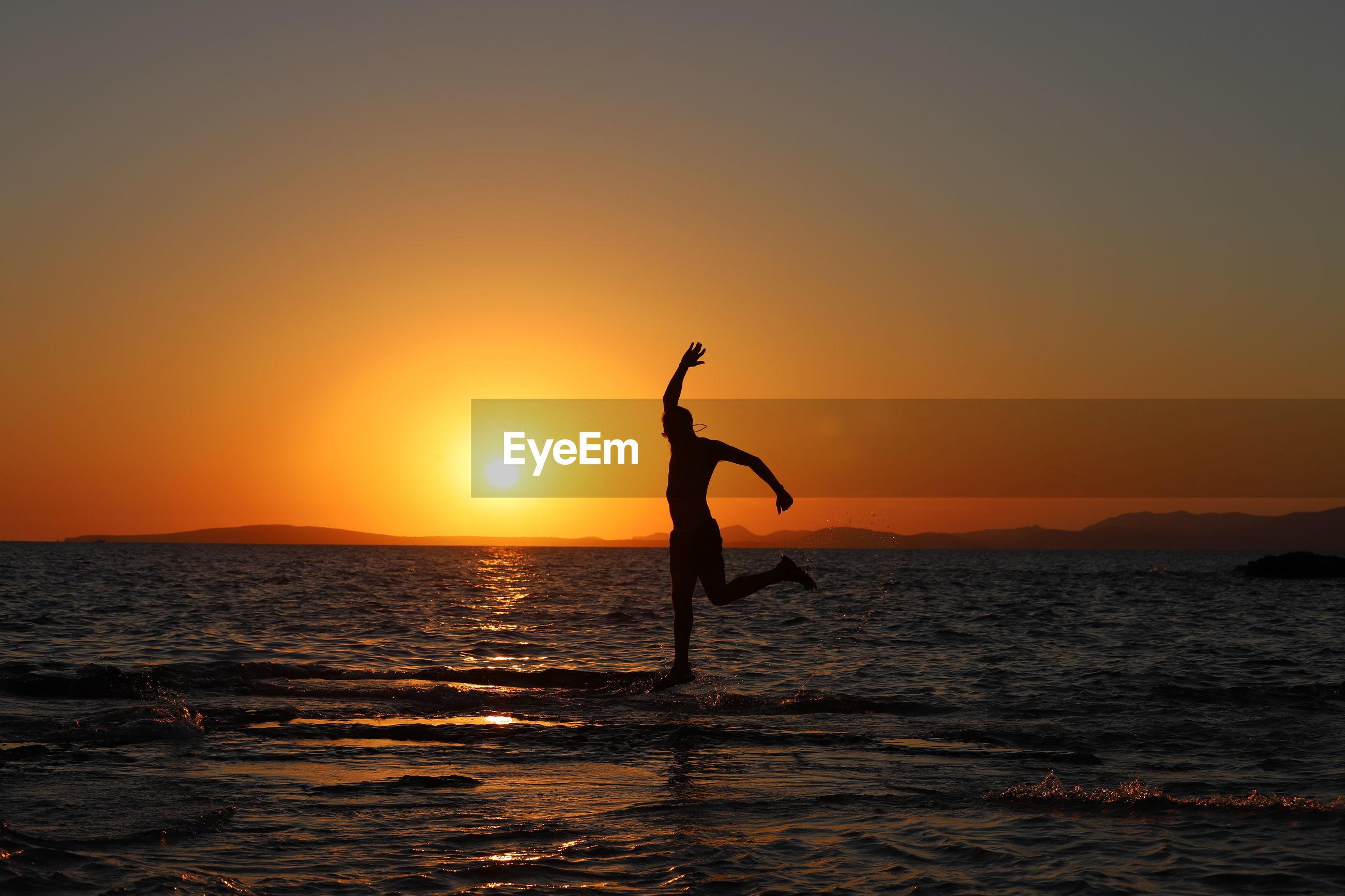 SILHOUETTE WOMAN ON BEACH AGAINST ORANGE SKY