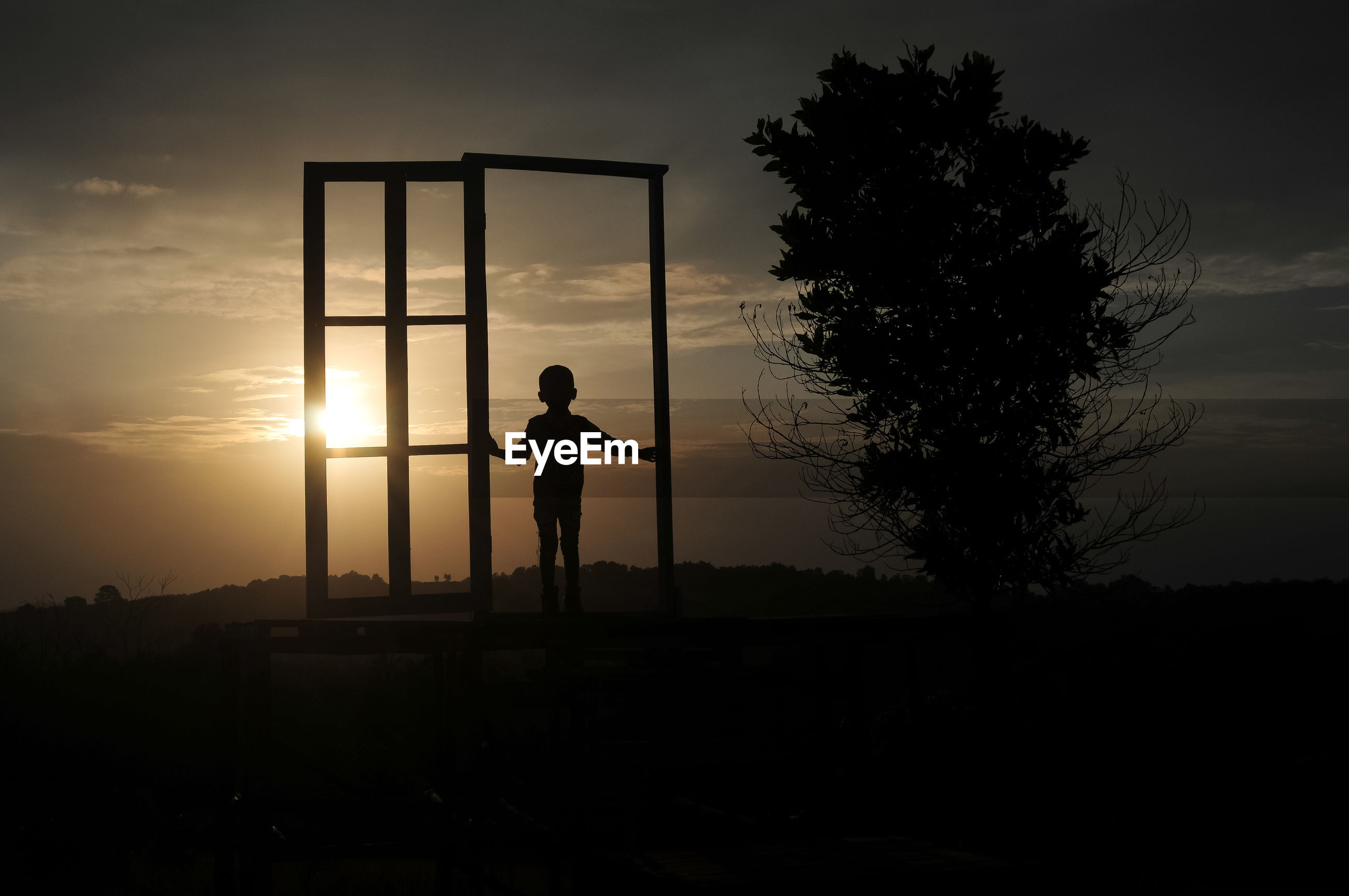 Silhouette boy walking at gate on field against sky during sunset