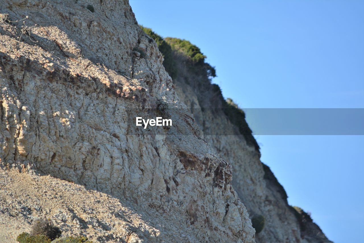sky, rock, mountain, low angle view, rock - object, nature, solid, clear sky, day, no people, blue, sunlight, textured, outdoors, rock formation, tree, rough, beauty in nature, tranquility, land, mountain peak, formation, high