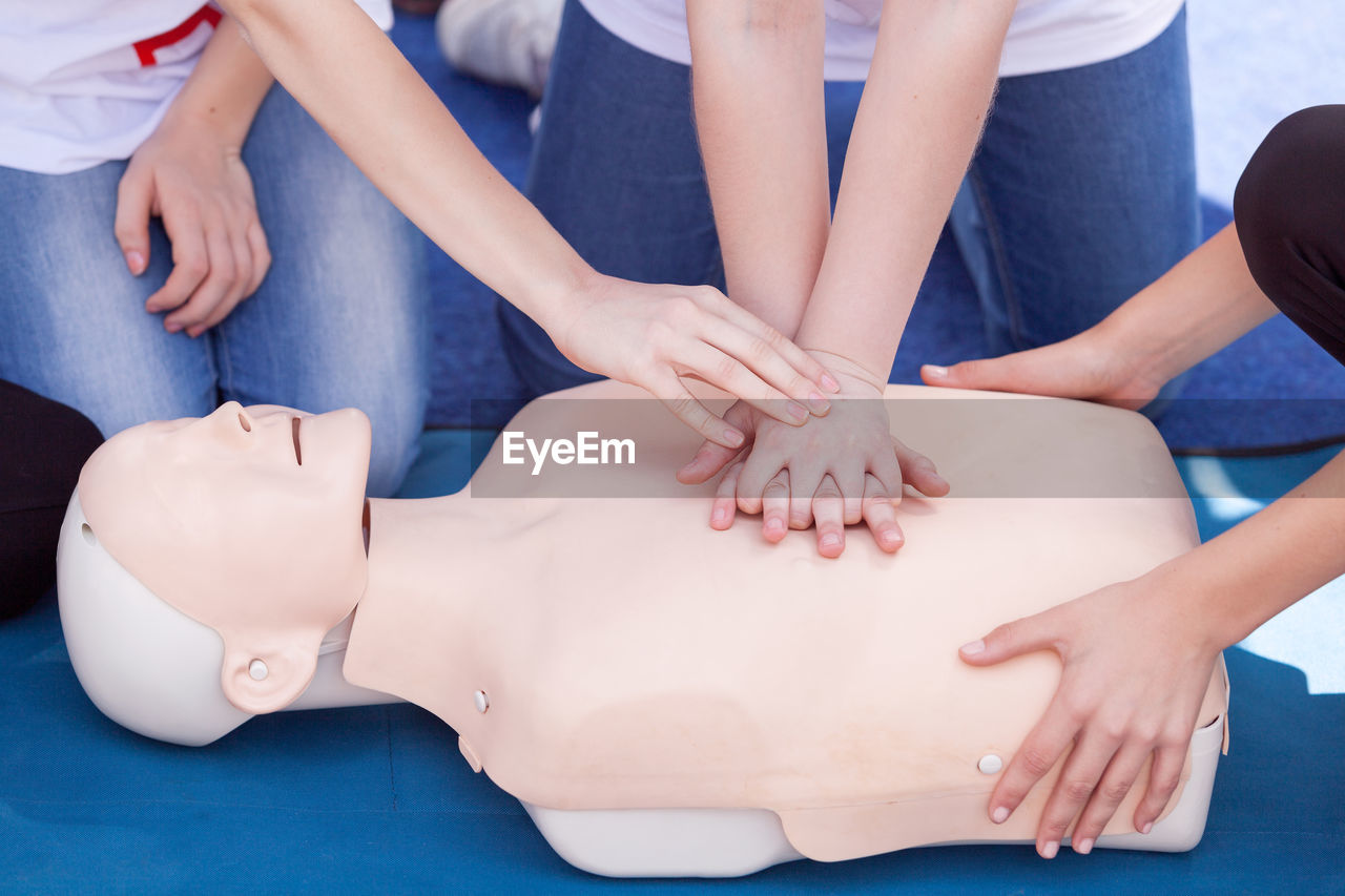 Midsection of paramedics performing cpr on mannequin