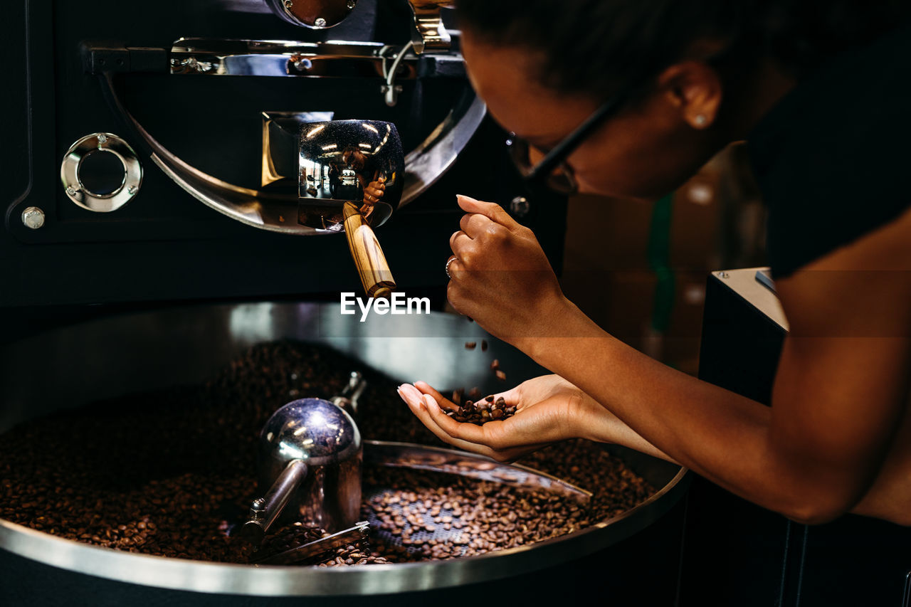 Close-Up Of Woman With Roasted Coffee Beans In Machinery At Cafe