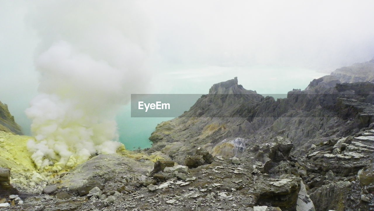 geology, mountain, physical geography, smoke - physical structure, nature, volcano, volcanic crater, erupting, sulphur, landscape, active volcano, emitting, beauty in nature, day, outdoors, steam, rock - object, volcanic landscape, scenics, no people, tranquility, power in nature, sky, hot spring