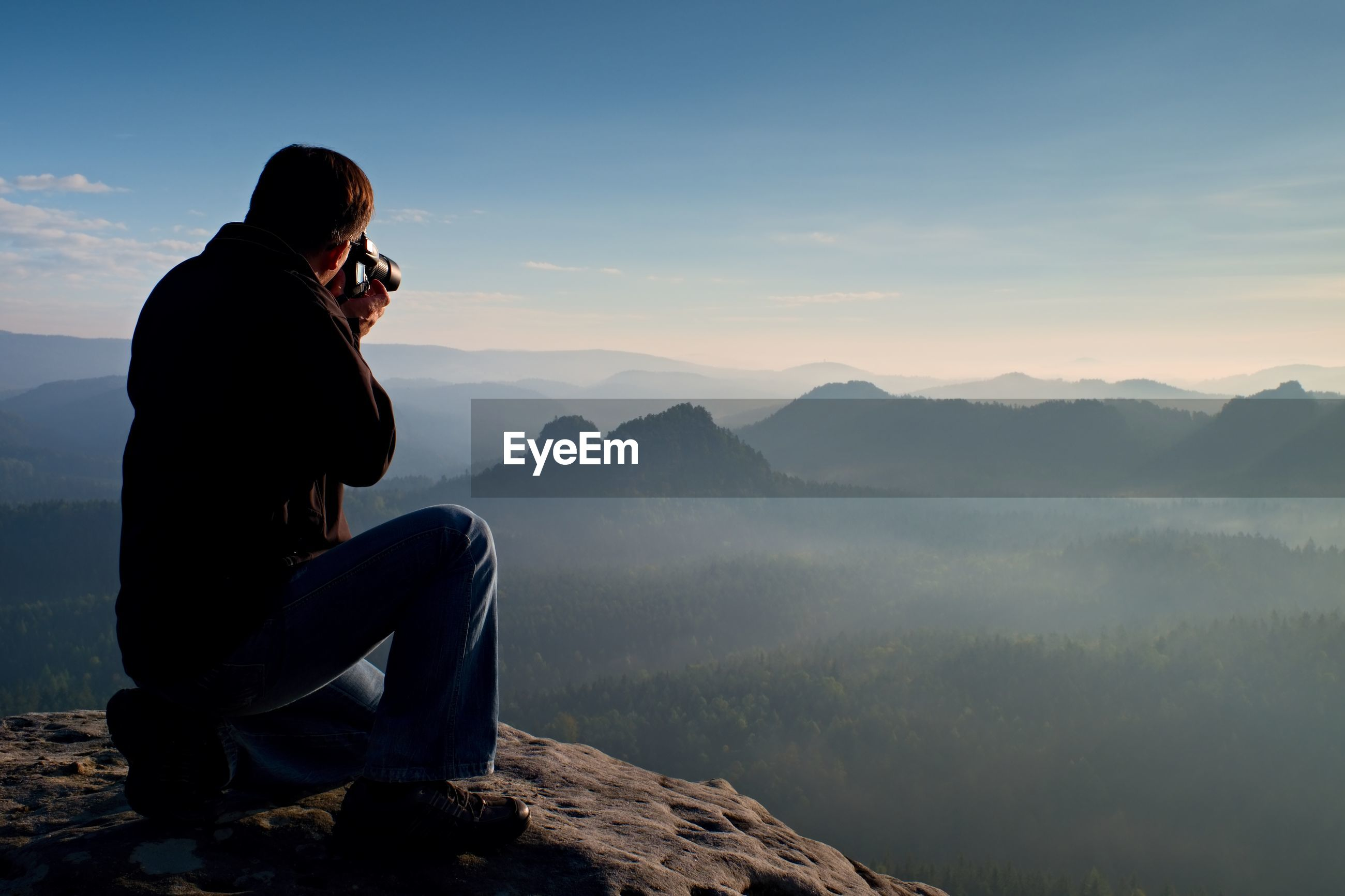 Dark hair man is taking photo by big mirror camera on the neck on the peak of mountains