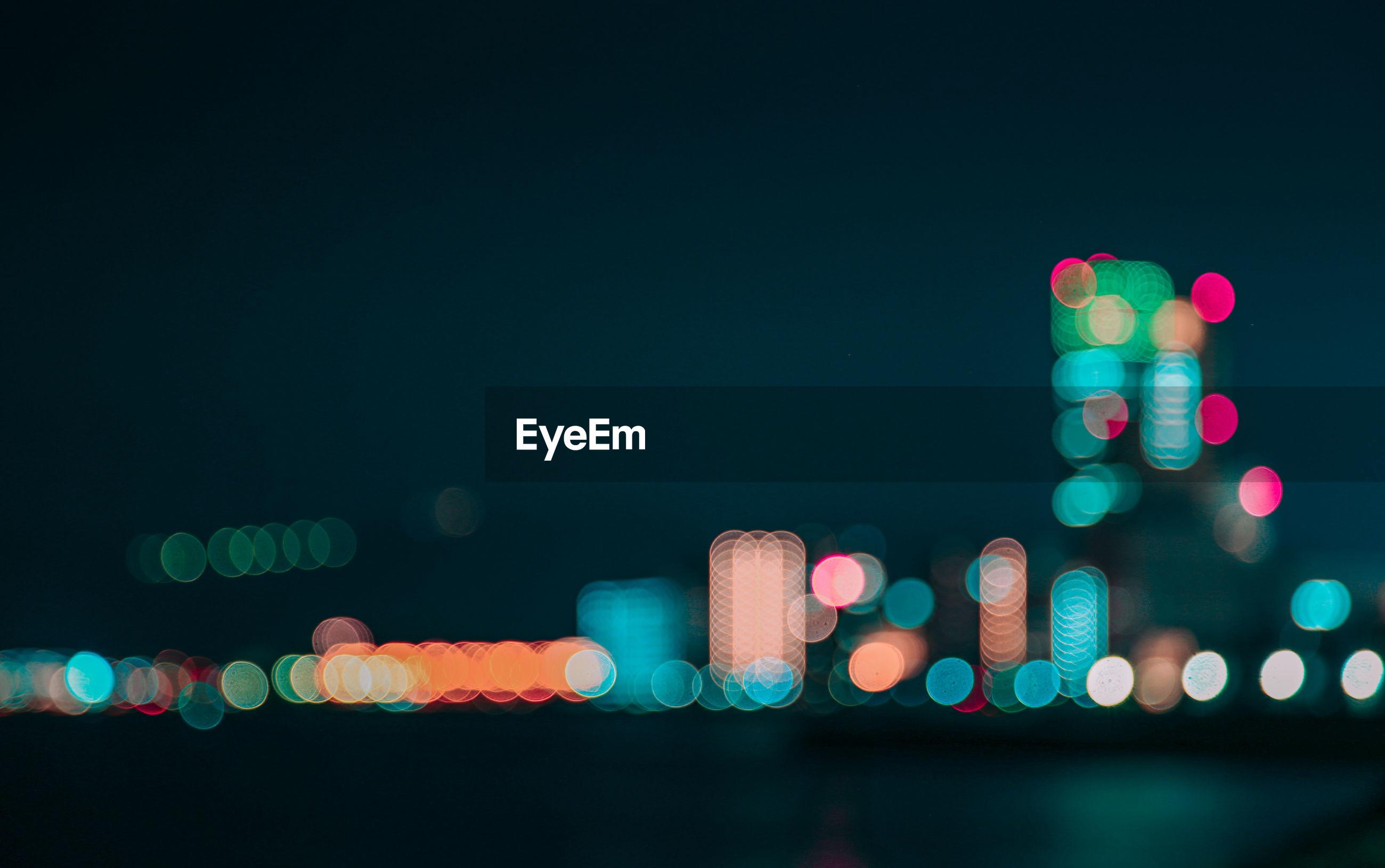 Defocused image of illuminated lights in city against sky at night