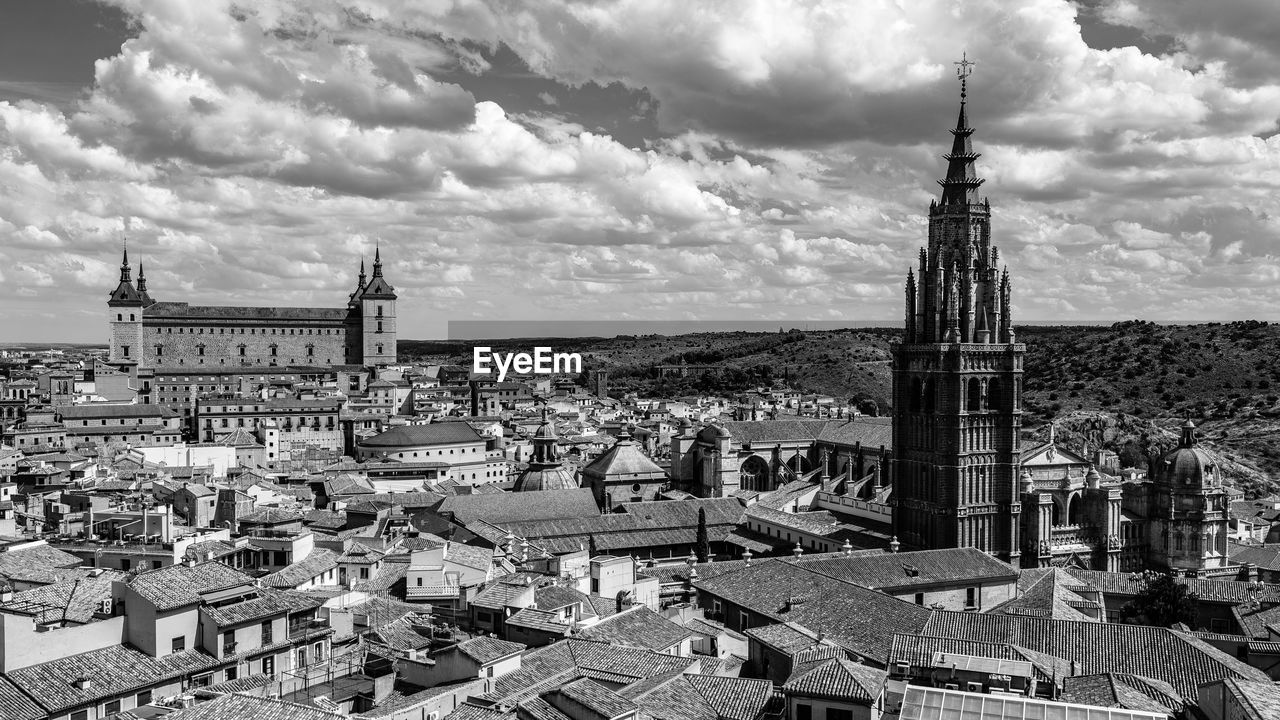 architecture, building exterior, built structure, cloud - sky, building, city, sky, place of worship, religion, cityscape, belief, spirituality, travel destinations, crowded, crowd, the past, tower, history, outdoors, spire, townscape, gothic style