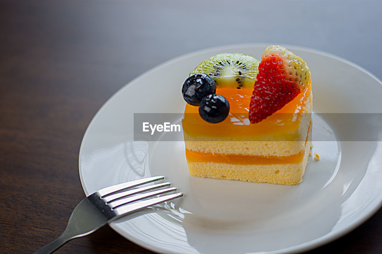 food and drink, eating utensil, food, fork, kitchen utensil, plate, fruit, table, sweet food, berry fruit, dessert, sweet, indulgence, freshness, still life, ready-to-eat, cake, baked, healthy eating, temptation, no people, slice of cake, cheesecake, breakfast