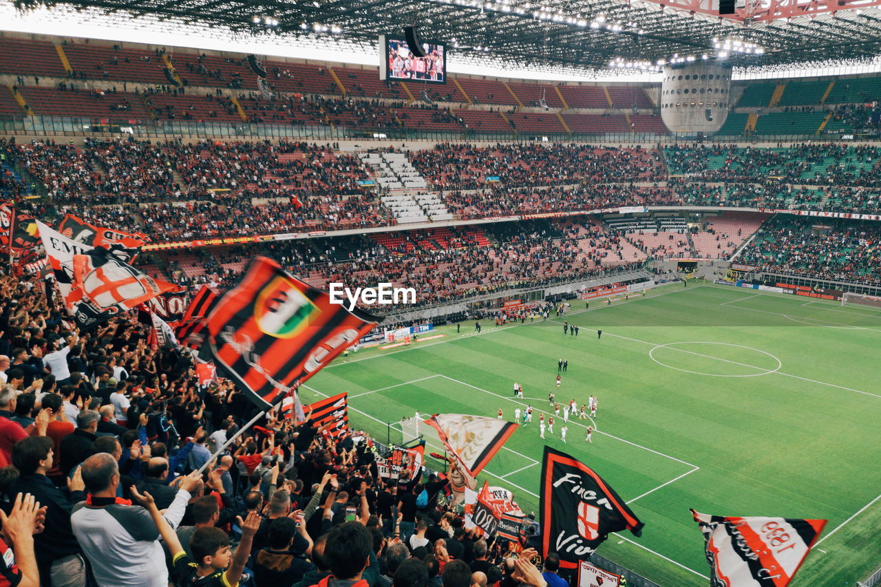 stadium, sport, group of people, crowd, large group of people, spectator, team sport, real people, high angle view, soccer, men, architecture, adult, fan - enthusiast, competition, grass, looking, emotion, positive emotion, outdoors, watching, excitement, match - sport, encouragement