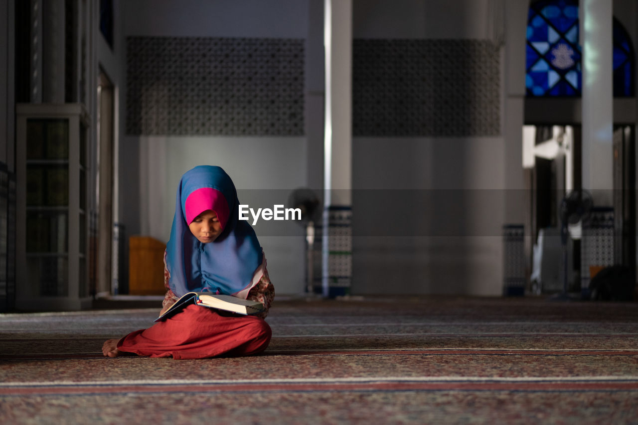 Girl In Hijab Reading Book While Sitting At Mosque