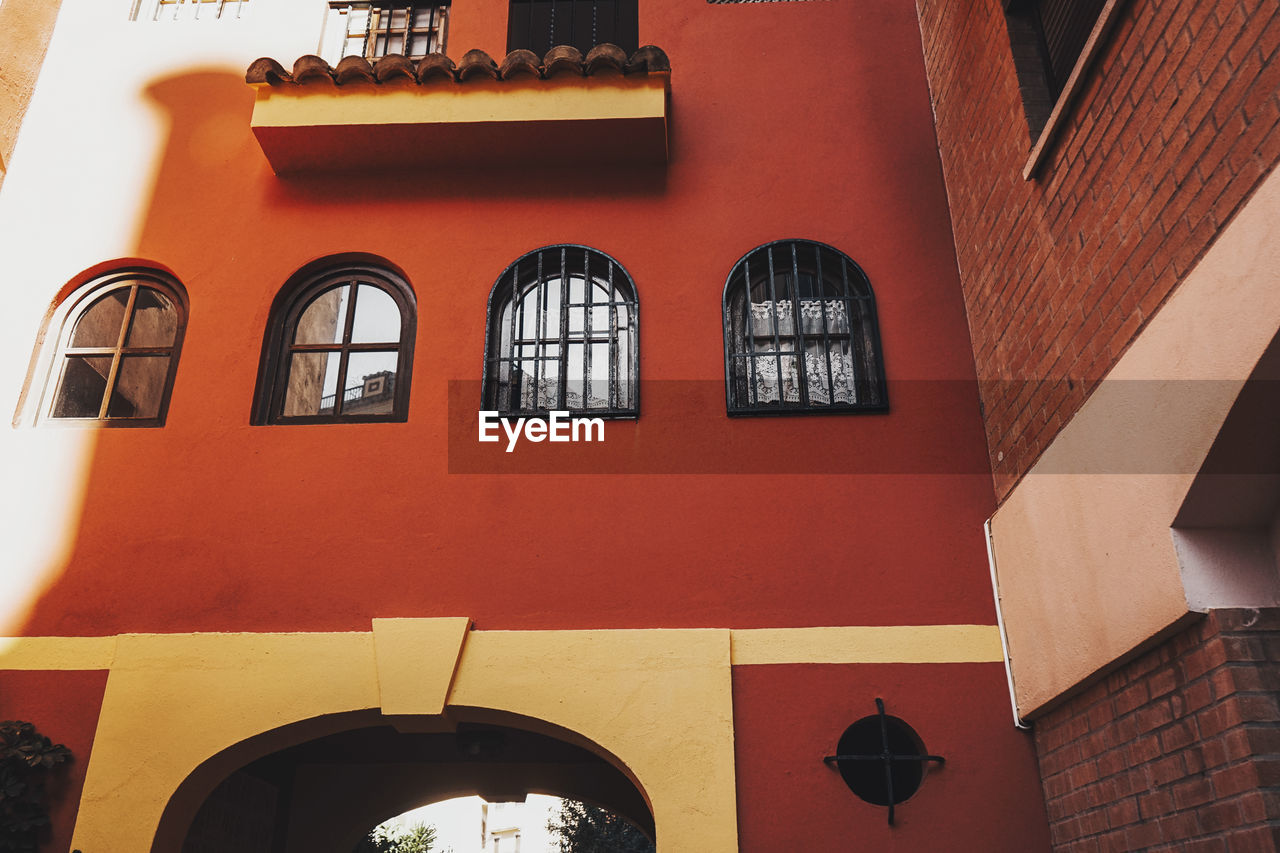 LOW ANGLE VIEW OF RED BUILDING WITH WINDOWS