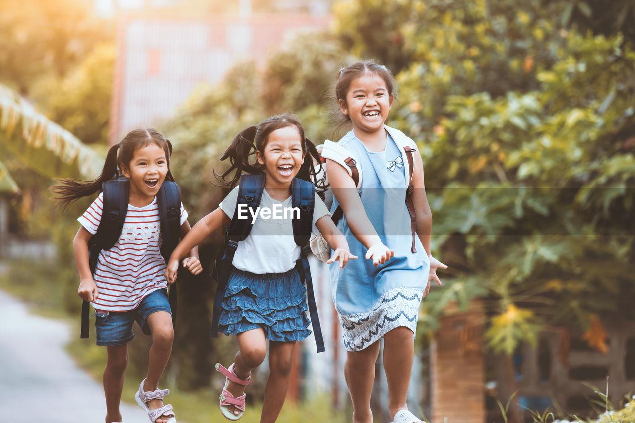 Happy Backpack Siblings Running On Road