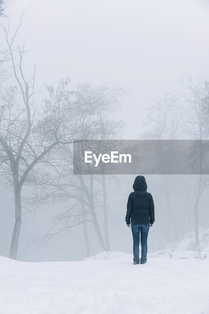 cold temperature, winter, snow, rear view, tree, full length, real people, one person, plant, warm clothing, beauty in nature, nature, land, leisure activity, lifestyles, white color, fog, clothing, outdoors, extreme weather