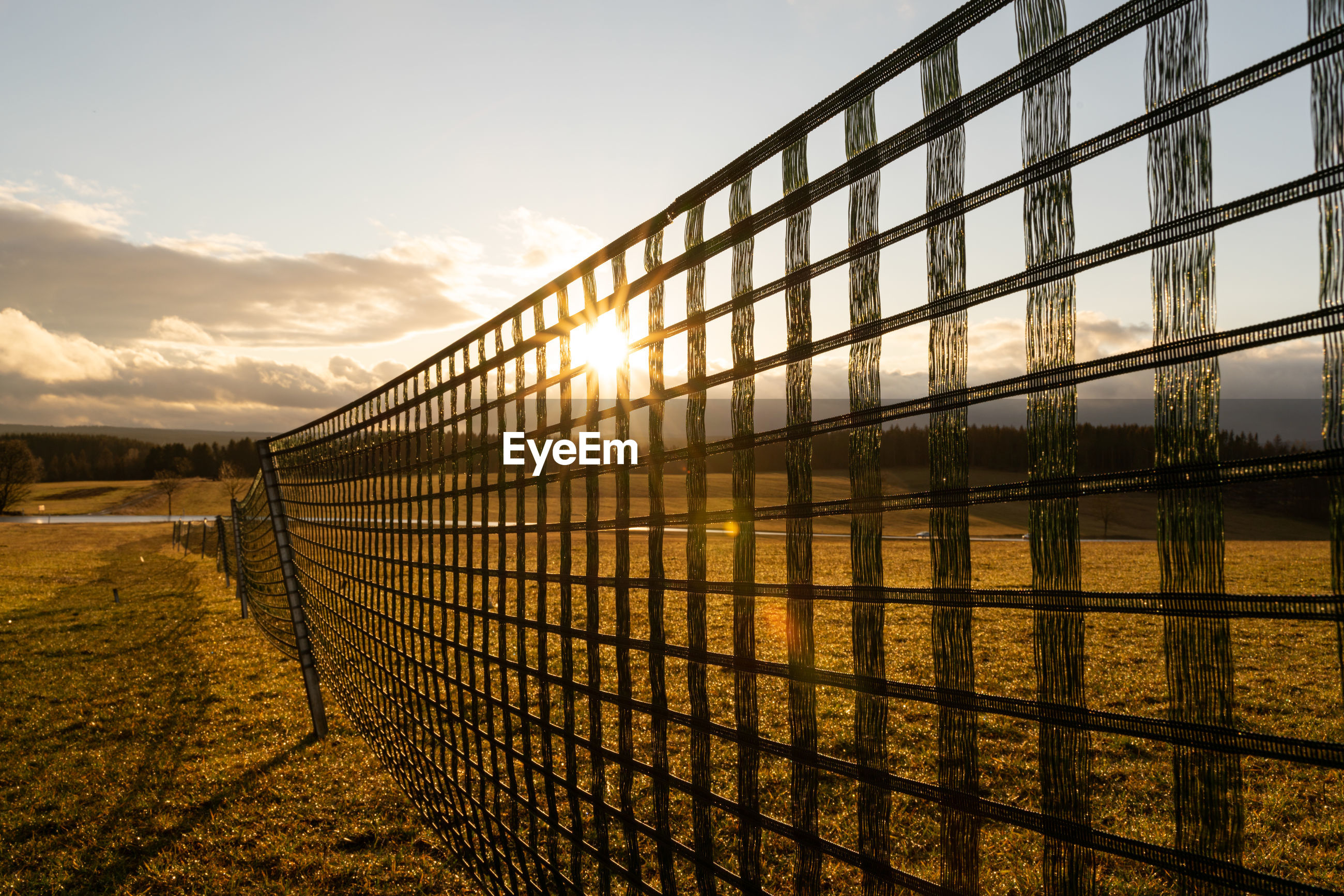 Fence against sky during sunset