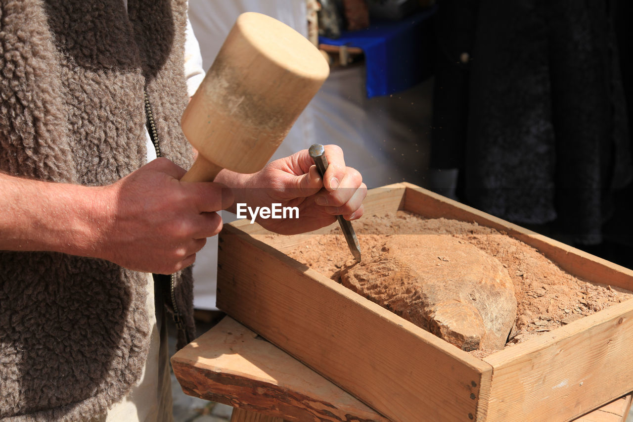 MIDSECTION OF MAN WORKING IN WOOD