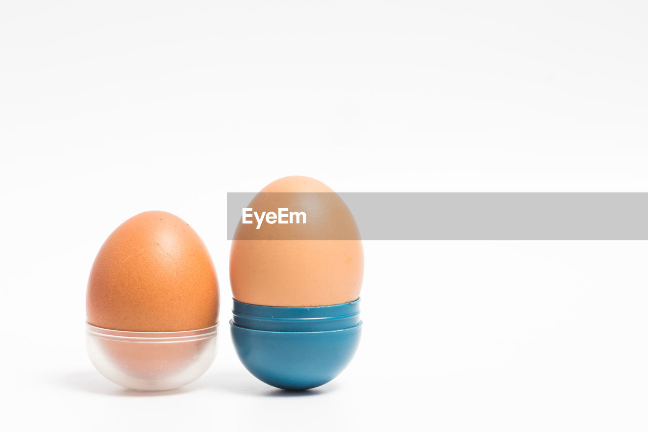 white background, egg, studio shot, food and drink, food, wellbeing, copy space, freshness, indoors, healthy eating, still life, close-up, raw food, no people, brown, cut out, vulnerability, fragility, group of objects, eggcup, boiled egg, breakfast