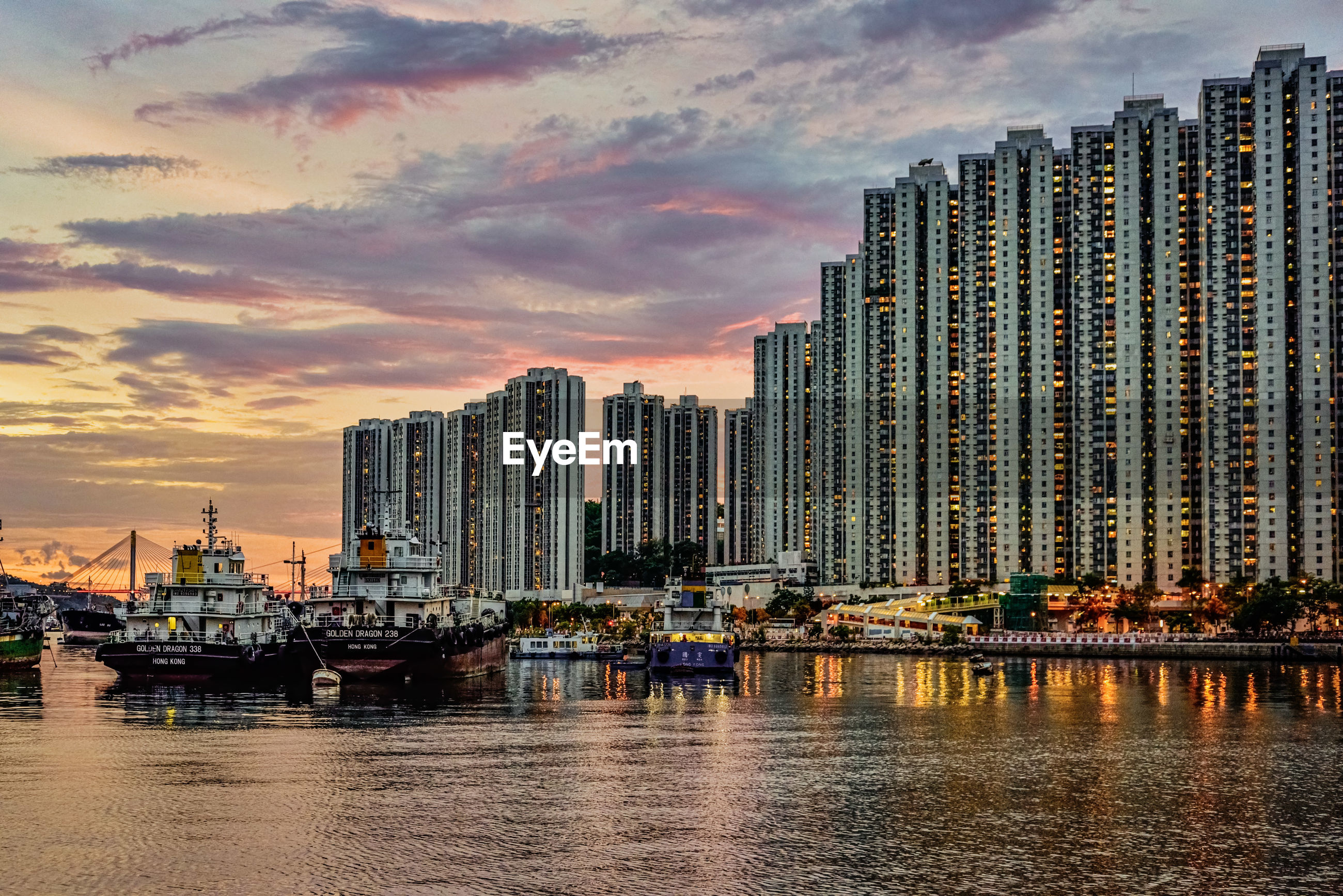 MODERN BUILDINGS BY SEA AGAINST SKY AT SUNSET
