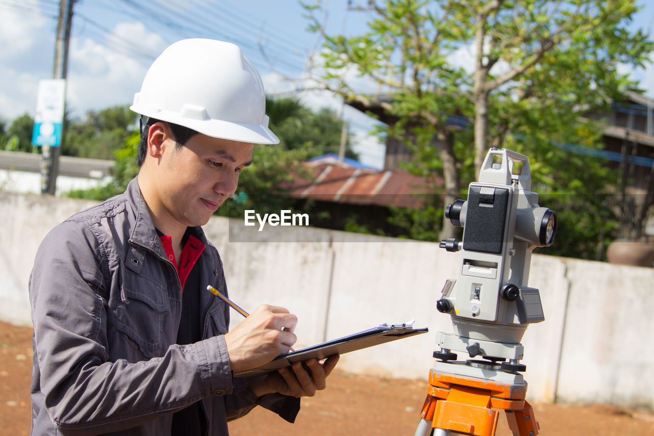 Engineer writing on paper by theodolite at construction site